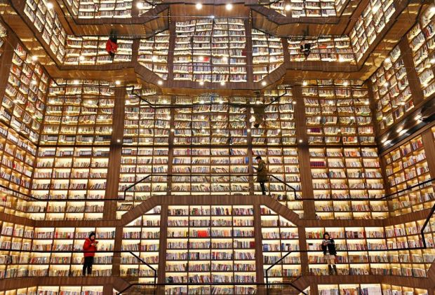 People stand and read books in a giant bookstore