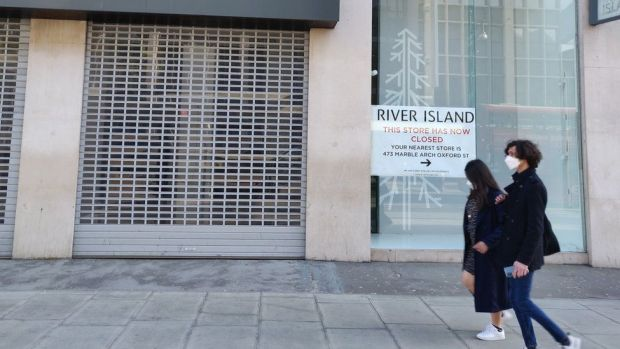 Two people walk past a boarded up River Island store on Oxford Street