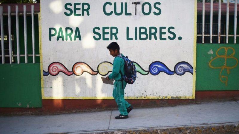 """Un niño mexicano camina frente un cartel: """"Ser cultos para ser libres""""."""