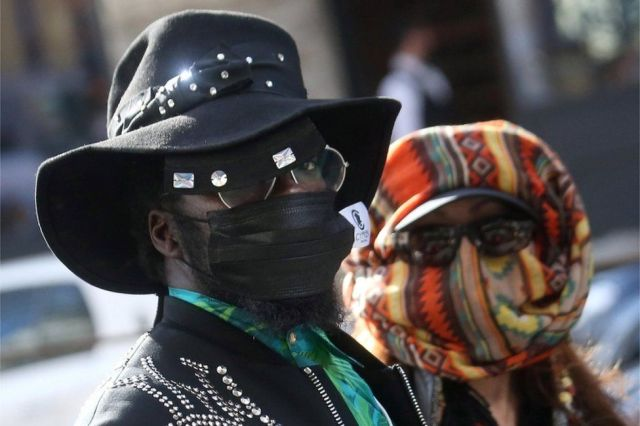 A man and a woman wear sunglasses and improvised masks at Milan Fashion Week.