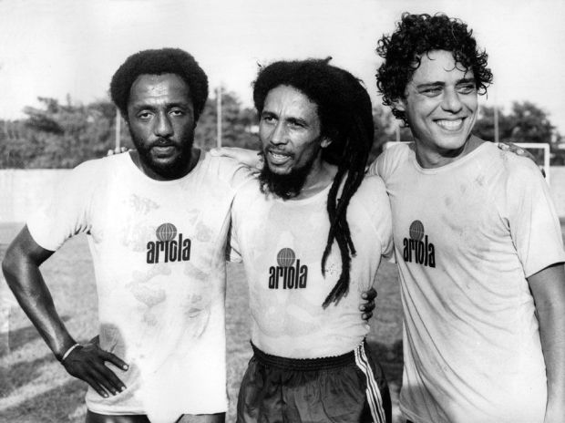 Bob Marley on a football field in Rio de Janeiro, Brazil, in 1980 with football player Paolo Cesar Caju and singer-songwriter Chico Buarque