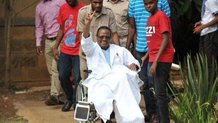Tanzania Opposition lawmaker Tundu Lissu waves from his wheelchair after giving a press conference surrounded by members of his family and supporters on January 5, 2018 at a hospital in the Kenyan capital, Nairob