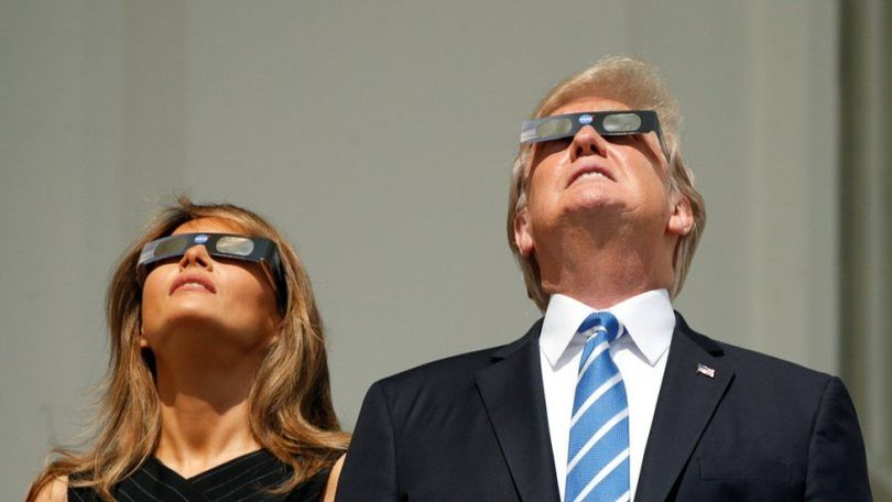 Donald and Melania Trump look upwards in their eclipse glasses
