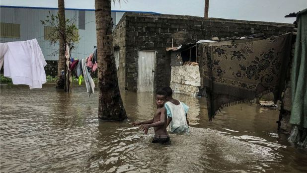 Children walk down a flooded road while sheets and covering are hung out to dry