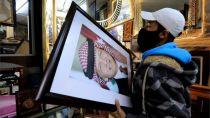 A frame maker in a frame shop displays pictures of King Abdullah II bin Al-Hussein king of Jordan, in Amman, Jordan, 4 April