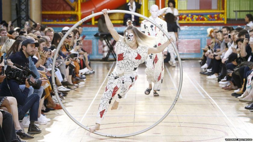 An acrobat in a hoop on the catwalk