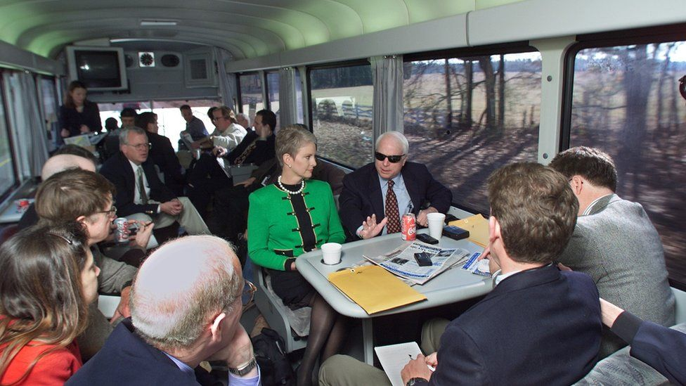 Republican presidential hopeful US Senator John McCain, (R-AZ), and his wife Cindy, (L), speak with reporters as they travel from Columbia to Sumter, South Carolina 07 Jan 2000