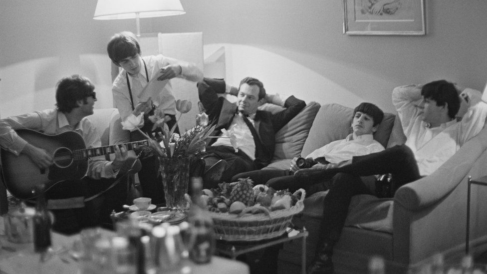 John Lennon, George Harrison, Brian Epstein, Ringo Starr and Paul McCartney relaxing on a sofa