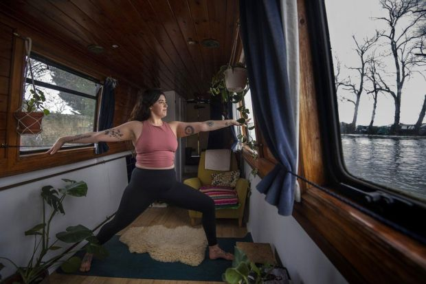 A woman holds a yoga pose in her narrowboat