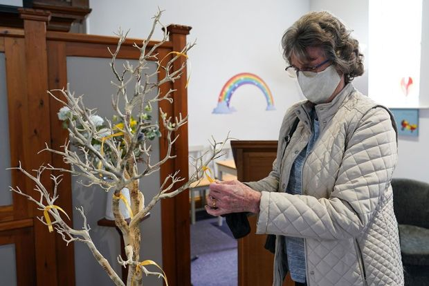 A woman ties a yellow ribbon to a memorial tree in a church