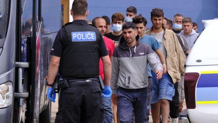 Migrants board a coach