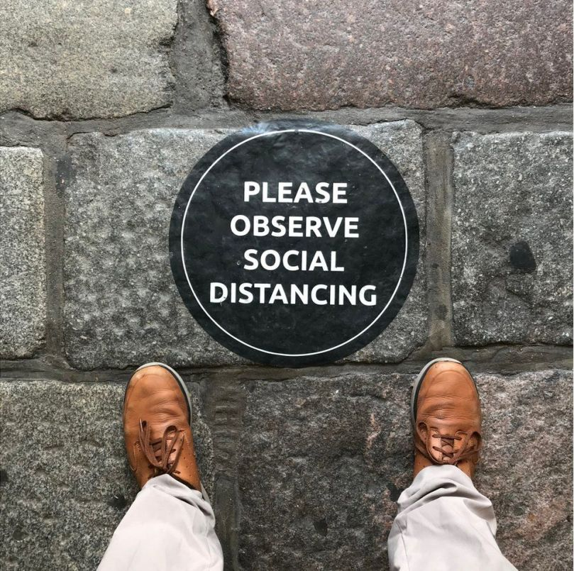 A sign on the ground that asks people to observe social distancing
