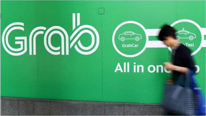 A woman walks past the Grab transport office in Singapore