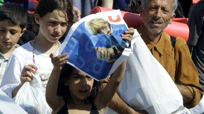 Një vajzë emigrante mban një poster të kancelares gjermane Angela Merkel ndërsa emigrantët ecin në qendër të Budapestit pasi kanë lënë zonën tranzit të stacionit kryesor të trenit, më 4 shtator 2015