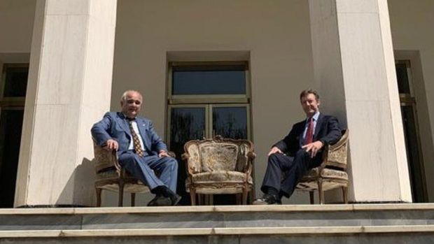 Russian and British ambassadors pose in chairs