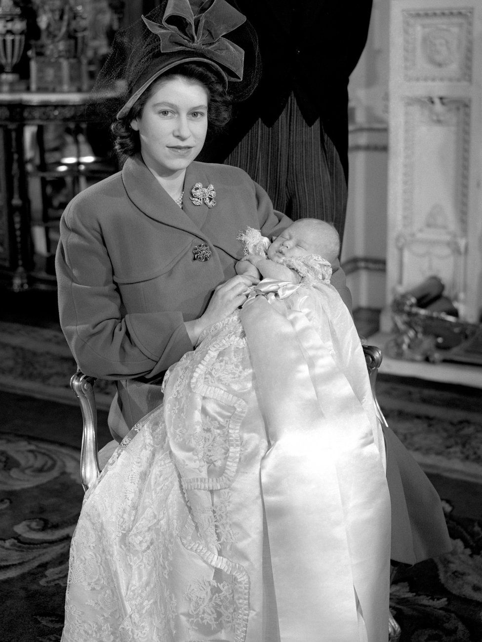 Princess Elizabeth holding her infant son, Prince Charles, after his christening ceremony at Buckingham Palace