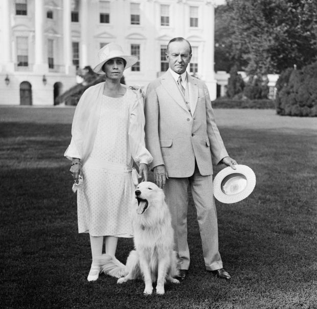 President Calvin Coolidge and First Lady Grace Coolidge stand in front of the White House with a dog in front of them that is yawning