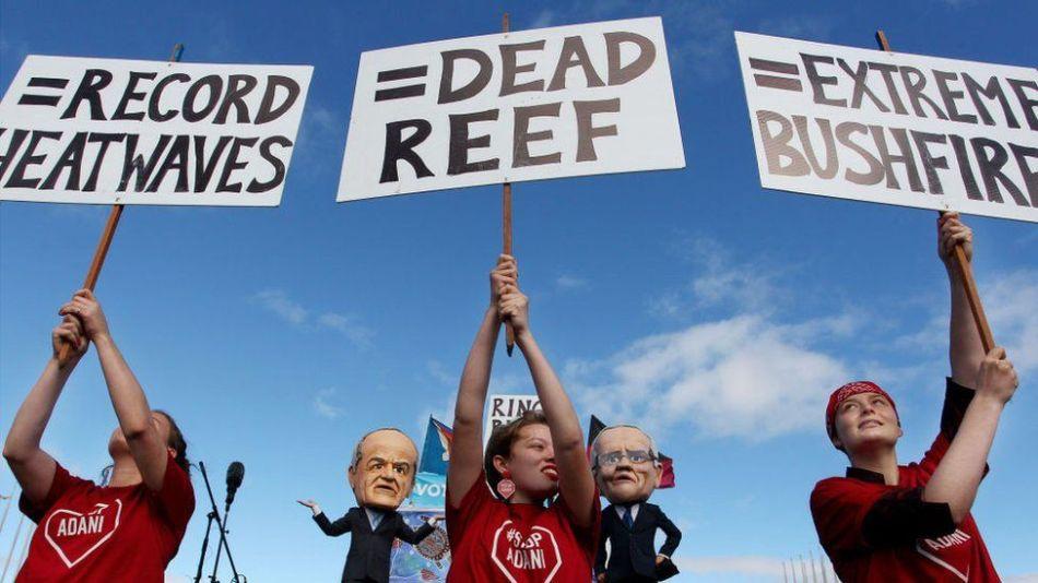 Giovani attivisti ambientali tengono cartelli di protesta davanti a comici vestiti come il leader laburista Bill Shorten e il primo ministro Scott Morrison il 5 maggio 2019 a Canberra, in Australia