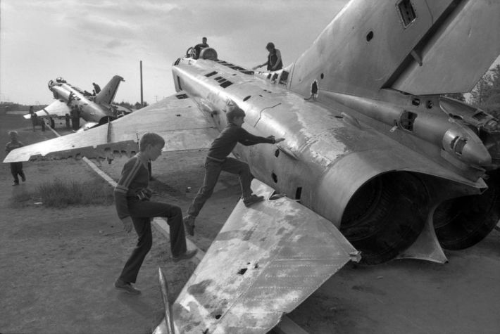 Boys playing on old Mig fighters