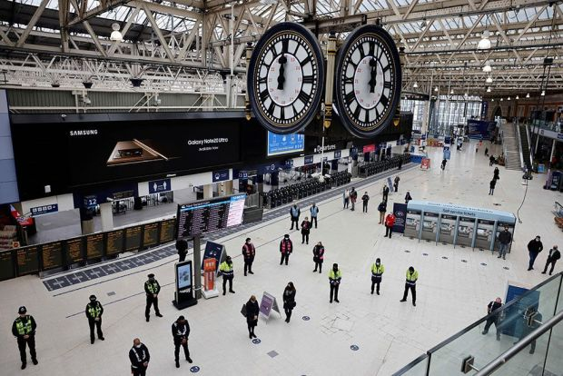 Commuters stand in the atrium of Waterloo station and observe a minute's silence