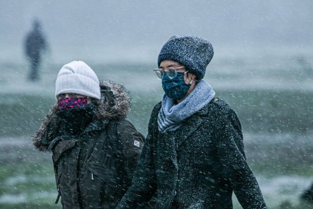 People wear face masks during a snow shower on Wimbledon Common, on 7 February 2021