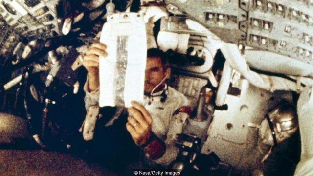Astronauta manipula embalagem dentro da nave