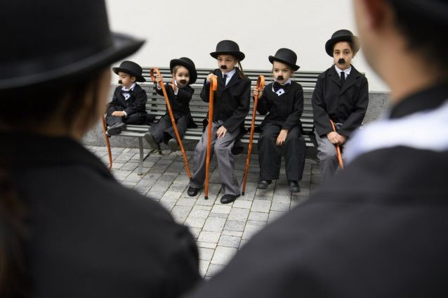 Children dressed as Charlie Chaplin pose for a group photo.