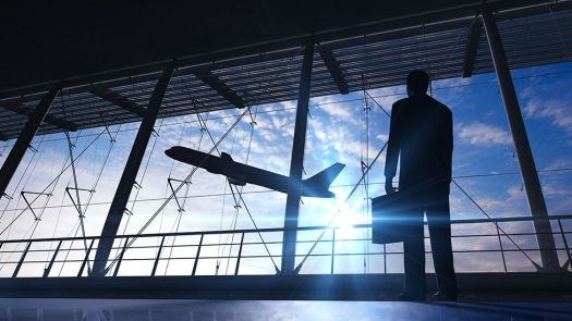Traveller in airport terminal with briefcase watching plane take off
