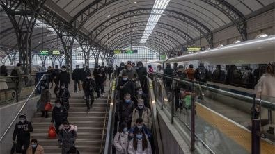 Passengers wearing protective face masks walk with their luggage after arriving to Hankou railway station, in Wuhan, China, 21 January 2021.