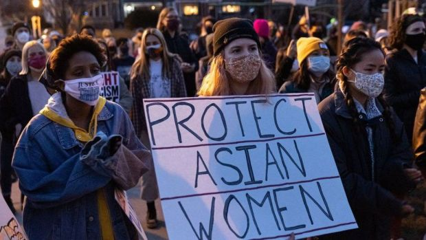 "A woman holds a sign during the ""Asian Solidarity March"" rally against anti-Asian hate in response to recent anti-Asian crime on March 18, 2021 in Minneapolis, Minnesota"
