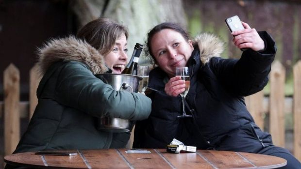 Women take a selfie with their drinks at The Fox on the Hill pub in London