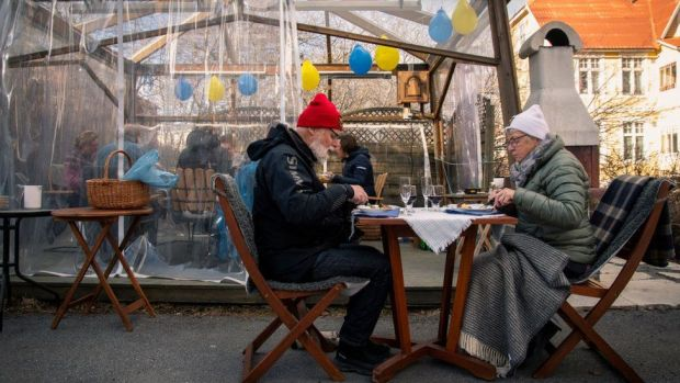 A couple eat at a cafe, 18 April 2020, in Ostersund, Sweden.