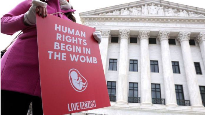 A pro-life activist holds a sign outside the US Supreme Court during the 48th annual March for Life January 29, 2021