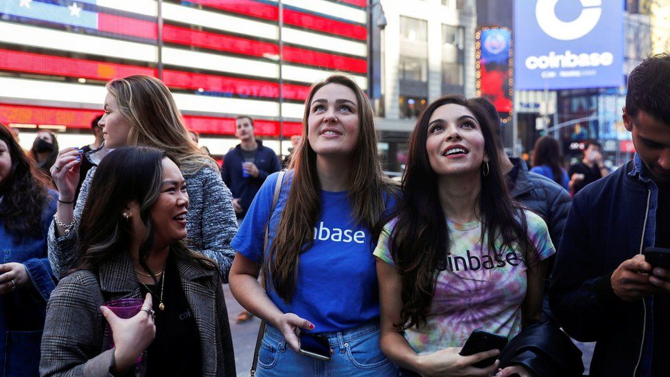 Employees of Coinbase Global Inc, the biggest U.S. cryptocurrency exchange, watch as their listing is displayed on the Nasdaq MarketSite jumbotron at Times Square in New York, U.S., April 14, 2021