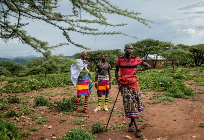 Deux guerriers Samburu parlent à Tiampati Leletit, qui a perdu 80 de ses chèvres à l'arrivée des criquets