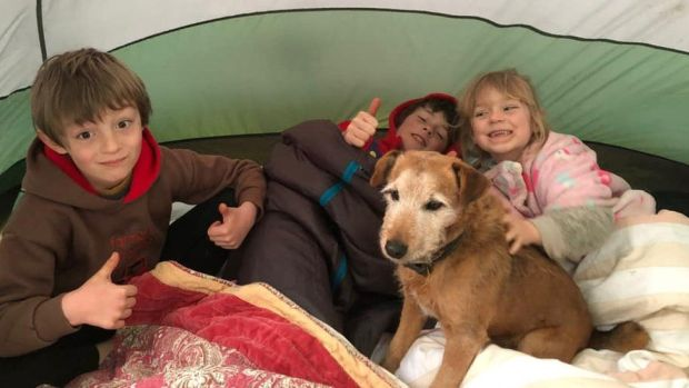 Three children with dog in tent