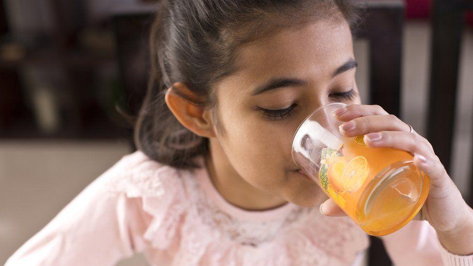 meyve suyu içen kız çocuğu