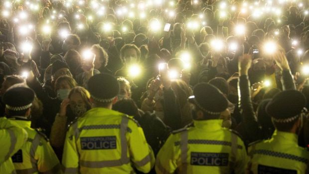 Police stand in front of a crowd of people who turn on their phone torches as they gather in Clapham Common, south London