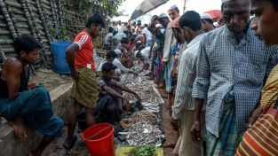 Rohingya refugees buy fish at a market place in Kutupalong refugee camp in Ukhia on October 8,