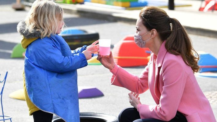 The Duchess of Cambridge interacts with a child during a visit to School 21 following its reopening