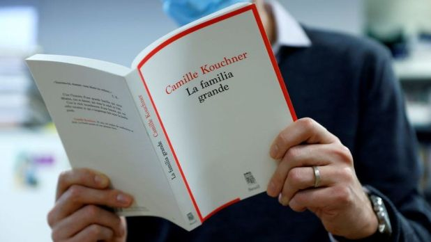 A man reads Camille Kouchner's book La Familia Grande in Paris on 5 January 2021