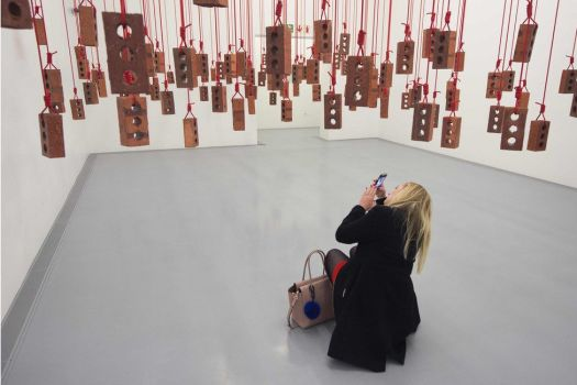 A visitor takes photos of an artwork by South African artist Kendell Geers, during the media opening of the Zeitz Museum of Contemporary Art Africa on September 15, 2017 in Cape Town.