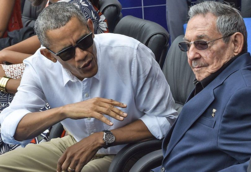 """US President Barack Obama speaks next to Cuban President Raul Castro (R) during a Major League baseball exhibition game between the Tampa Bay Rays and the Cuban national team at the Latinoamericano stadium in Havana on March 22, 2016. Obama praised the bravery of Cuban dissidents Tuesday in a meeting at the US embassy in Havana, although opponents back home dismissed the event as a """"token"""" gesture. AFP PHOTO / Nicholas KAMM / AFP PHOTO / NICHOLAS KAMM (Photo credit should read NICHOLAS KAMM/AFP via Getty Images)"""