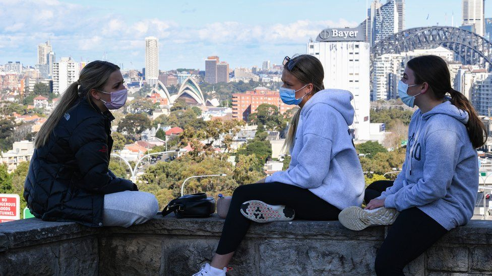 Three girls wearing face masks sit above the Bradfield Highway in the suburb of North Sydney with the city in the background on July 07, 2021 in Sydney, Australia.