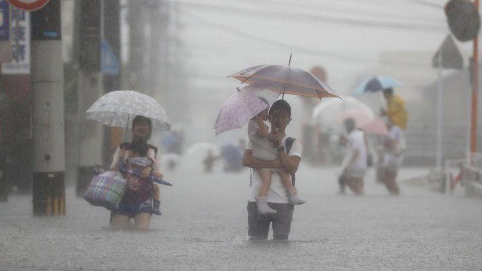 Local residents walk in a road flooded by heavy rain in Kurume, Fukuoka prefecture, western Japan