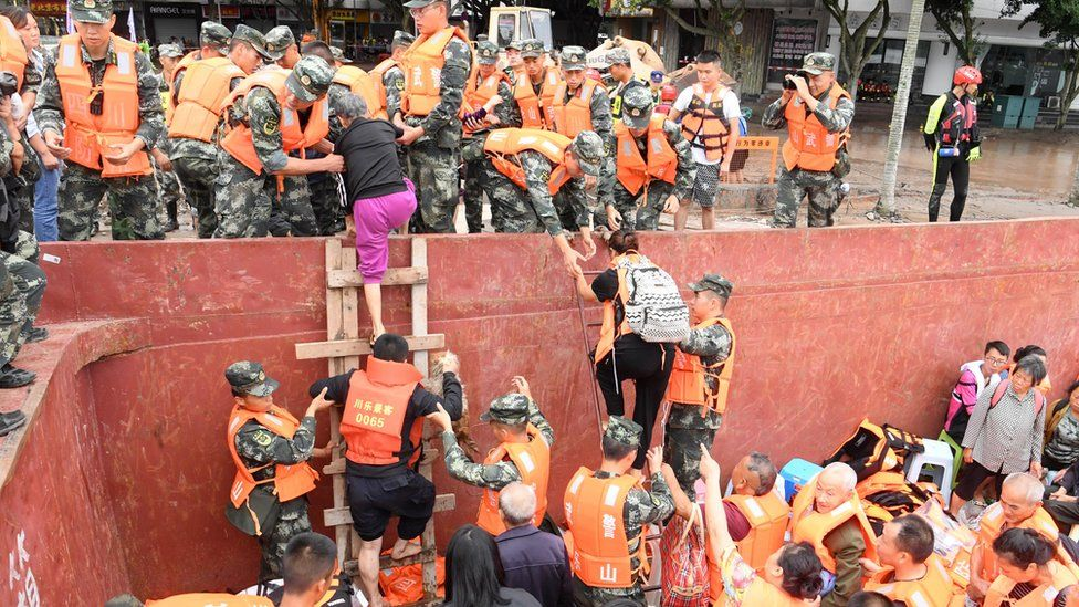 Rescuers help evacuated villagers get off boats onto land in Sichuan (18 August)