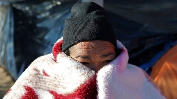 A Mexican migrant covers her face with a blanket as she and others camp at a park while waiting to apply for asylum in the US, in Ciudad Juarez on 17 December, 2019,