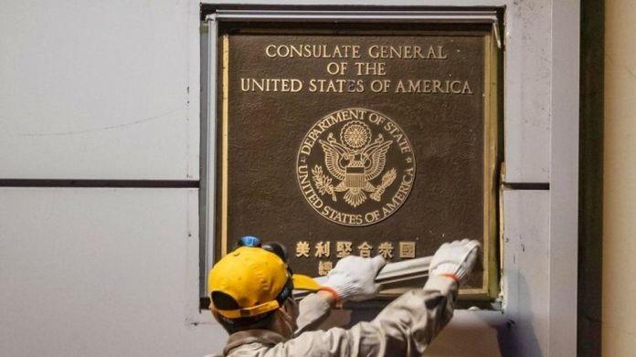 工作人员将领事馆外的徽标和铭牌拆除。