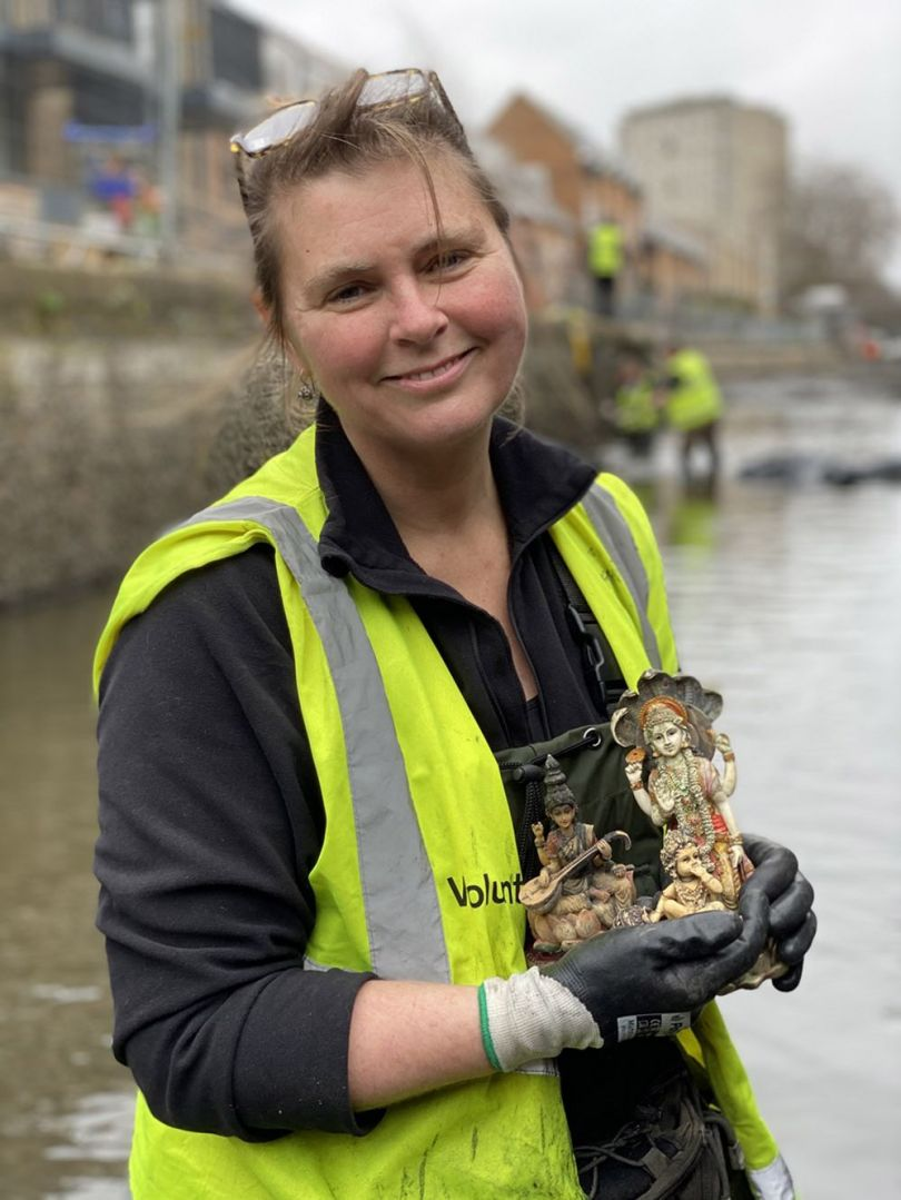 Monika Buttling-Smith holding three Hindu gods found into the canal
