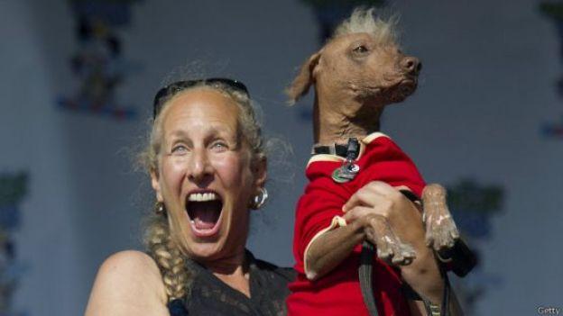 Rona Thau sostiene con gesto triunfante a su perro Morris.